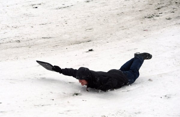 Belly sledding in a black suit, big hill, record snow day, Gas Works Park, Wallingford, Seattle,  Washington, USA by Wonderlane